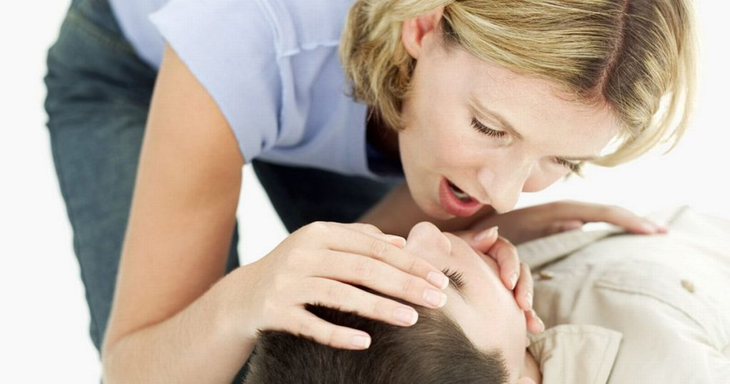 Woman performing-mouth-to-mouth-resuscitation-on-a-boy